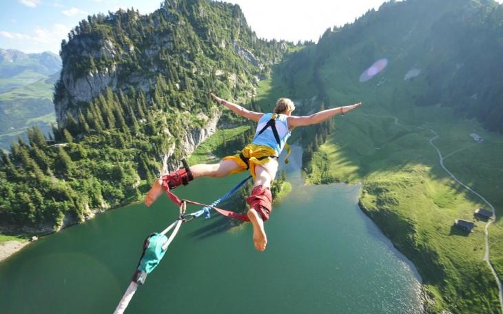 hombre saltando del bungee en un lago y montañas