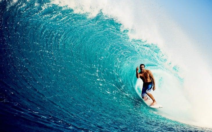 Hombre surfeando una ola en el mar