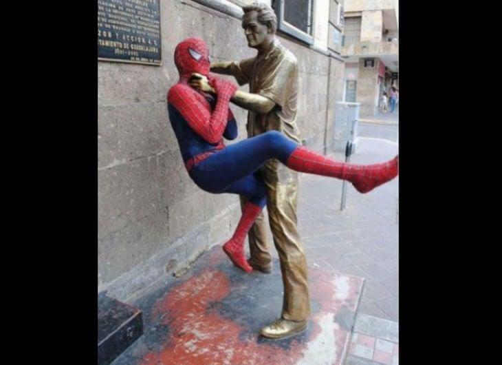 estatua maltratando a spiderman