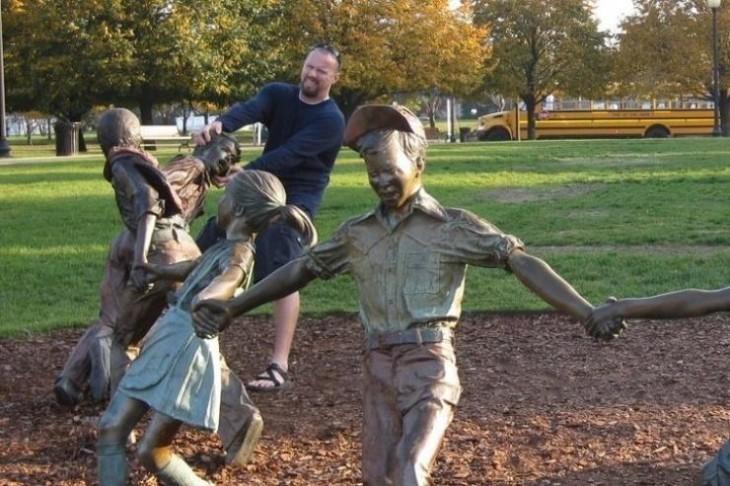 hombre pateando estatua de niños