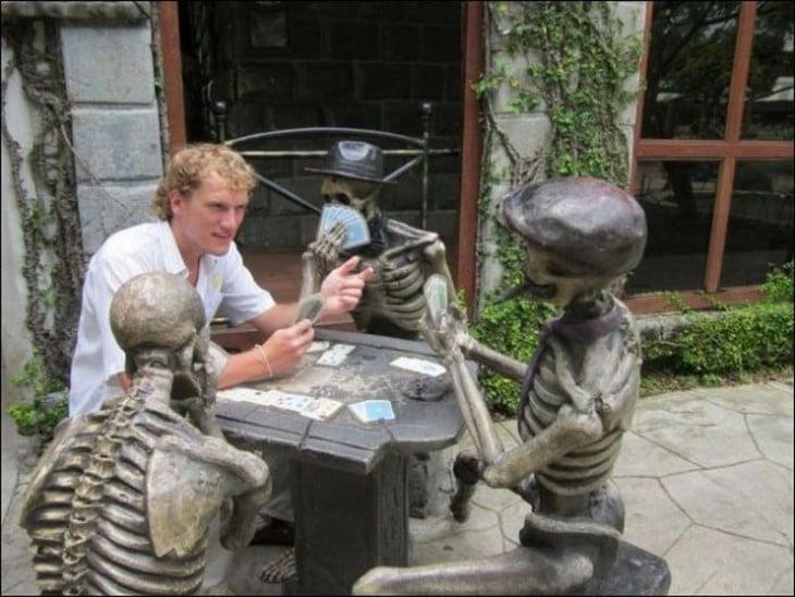 hombre jugando cartas con estatuas de calaveras