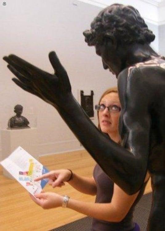 estatua dando indicaciones a mujer