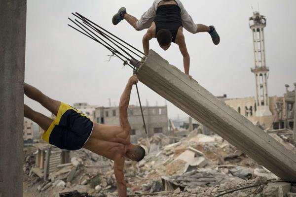 Bakr al-Makadmeh bandera y parados de manos en las ruinas de palestina