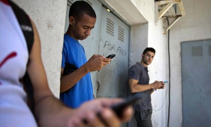 Jóvenes cubanos viendo sus celulares