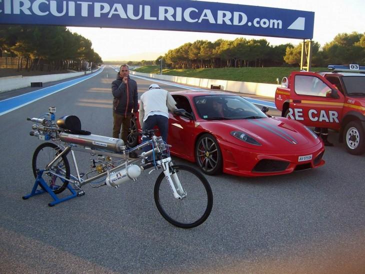 bicicleta con cohetes junto a ferrari