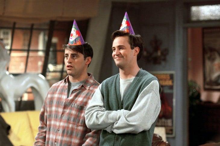 Chandler y Joey con gorros de fiesta