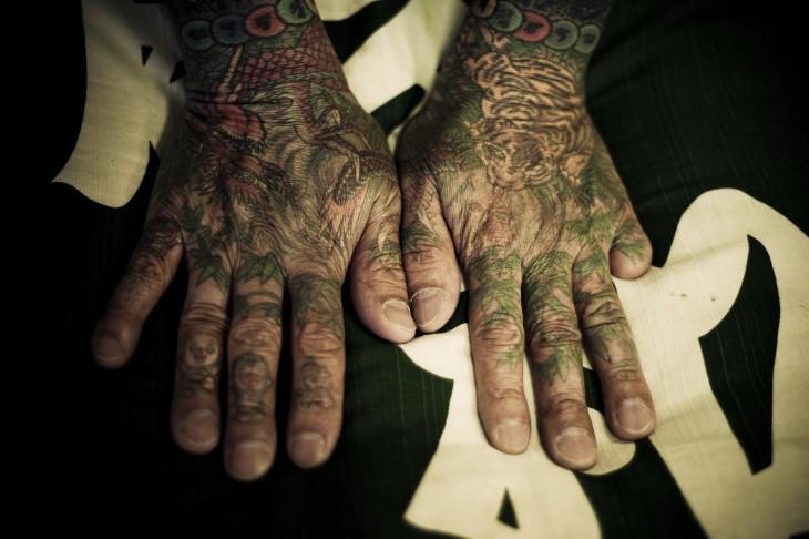 manos tatuadas de un yakuza, dedo cortado
