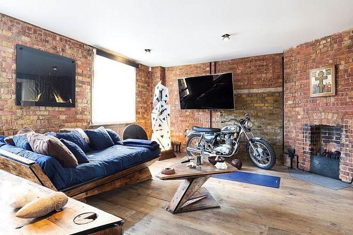 cuarto con sofá cama, tv y motocicleta