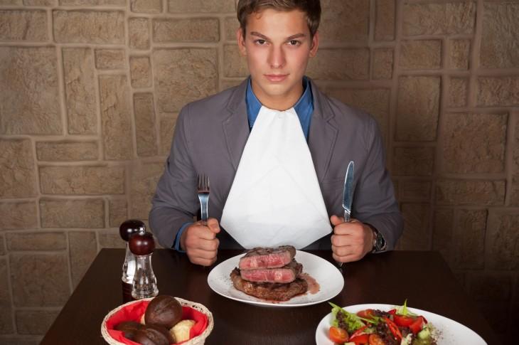 Hombre sentado comiendo un bistec