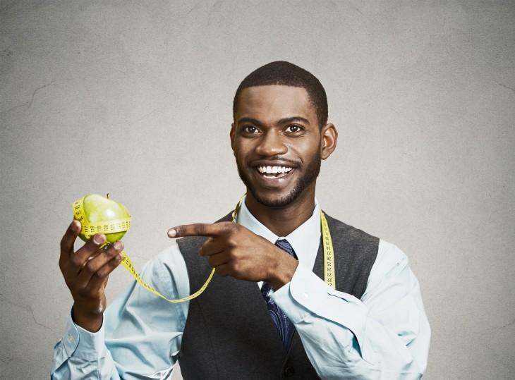 Hombre con una manzana y una cinta de medir