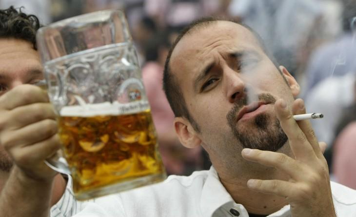 hombre fufmando y bebiendo cerveza