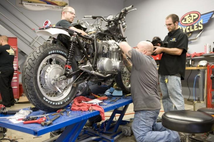 hombres reparando motocicletas