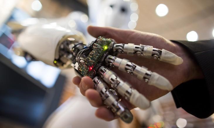 mano de robot saludando mano humana