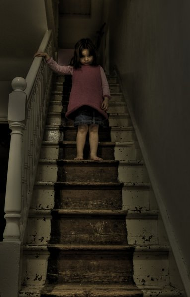 niña bajando las escaleras oscuras