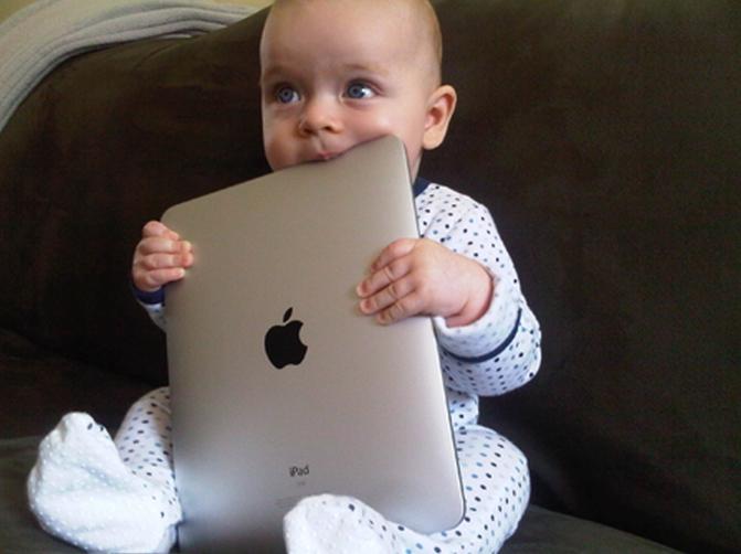 bebe masticando una laptop