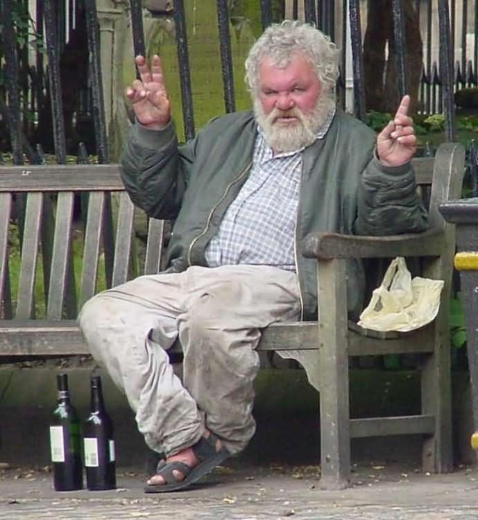 borracho de la calle alcoholico sentado en una banca