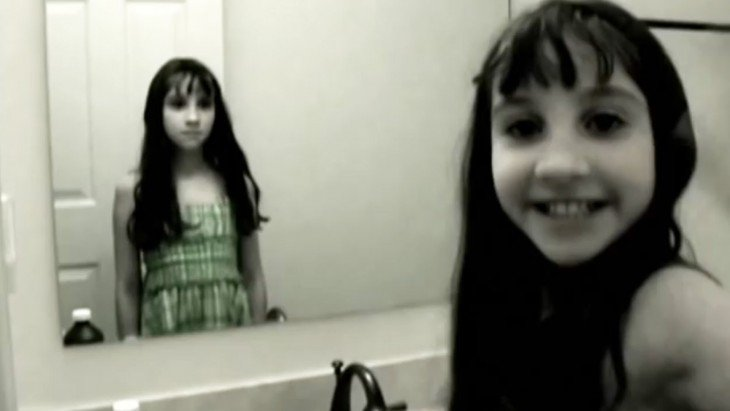 niña y su reflejo en el espejo