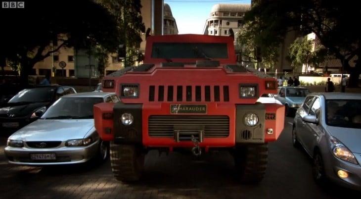 marauder rojo en la calle con autos de civiles