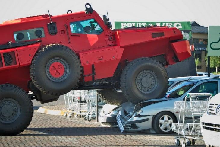 marauder rojo aplastando a dos autos en un estacionamiento