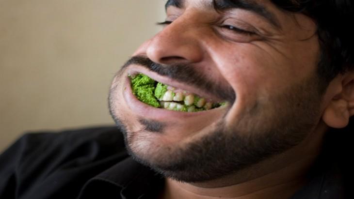 hombre masticando guasabi con la boca abierta