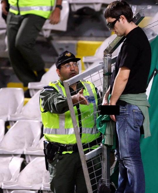 hombre orinando en gradas de estadio con policia a un lado