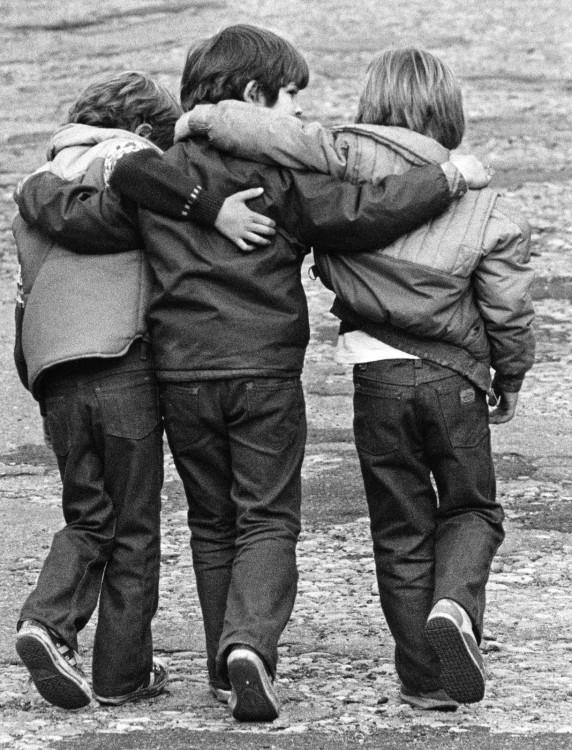 Niños abrazados van caminando