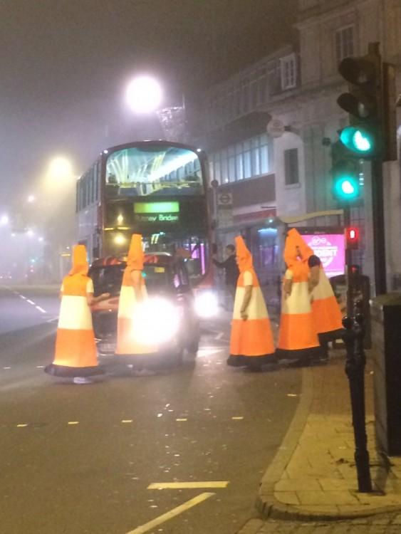 hombres disfrazados de conos de transito bloqueando trafico