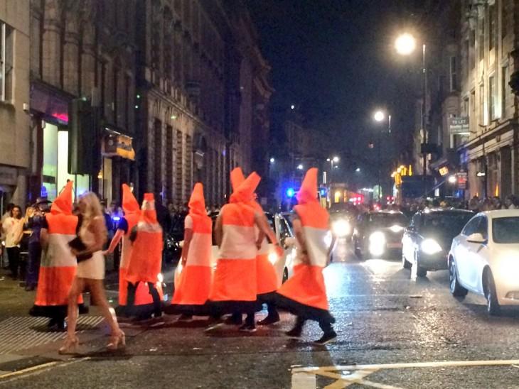 hombres disfrazados de conos de trafico