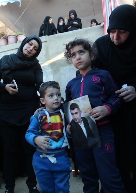 hijo de Adel Termos con foto de su padre