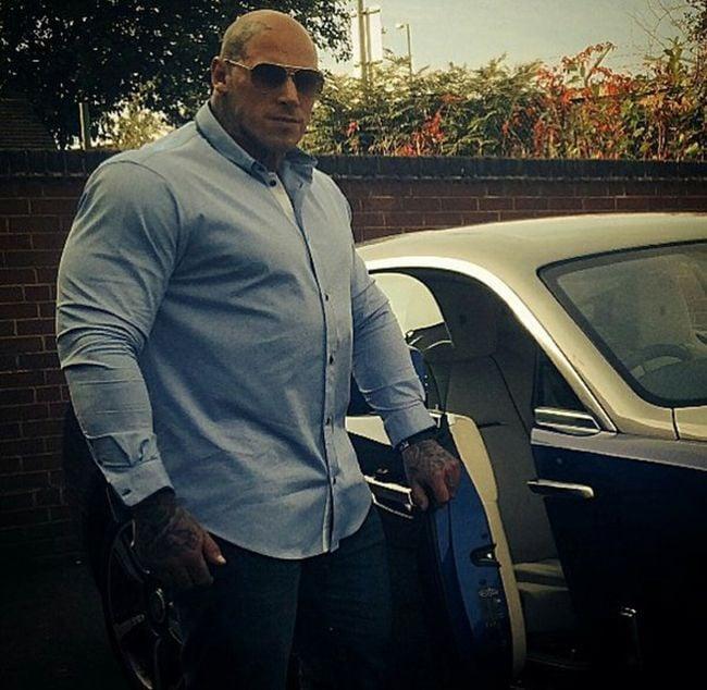 Martyn con camisa de vestir y su auto