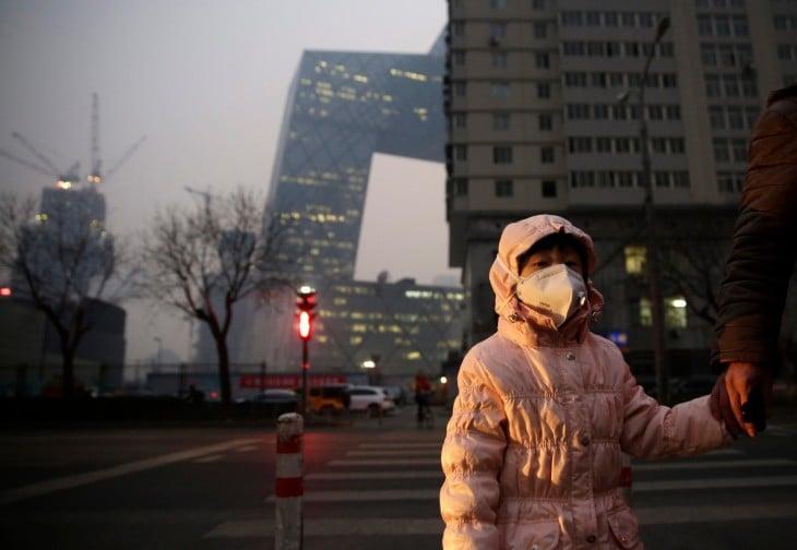 Niña china usa cubrebocas ante alta contaminación