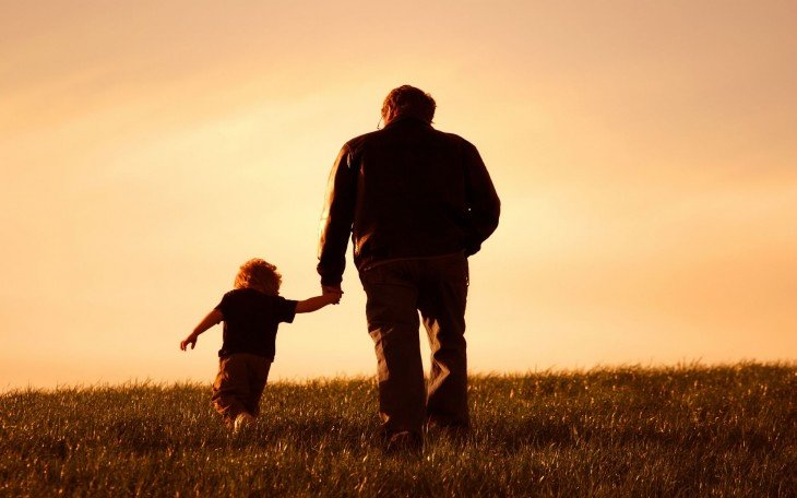Padre e hijo caminan al atardecer