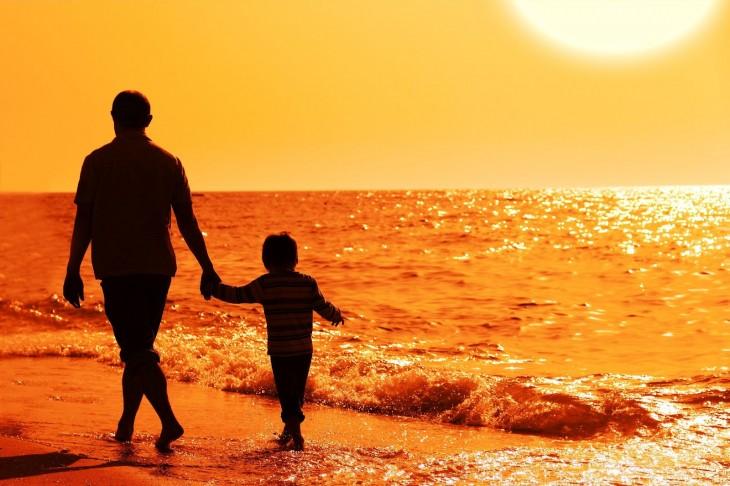 Padre e hijo caminan en la playa al atardecer