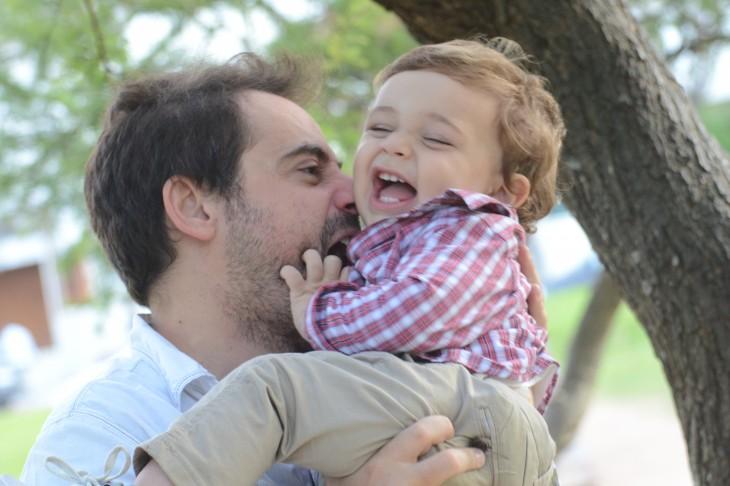 Niño ríe al jugar con su padre
