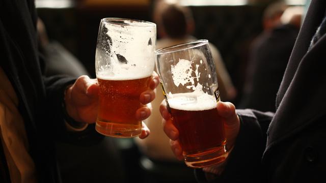 manos de dos personas con una cerveza brindando
