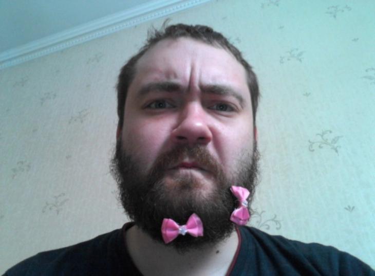 Hombre con broches en color rosa sobre su barba