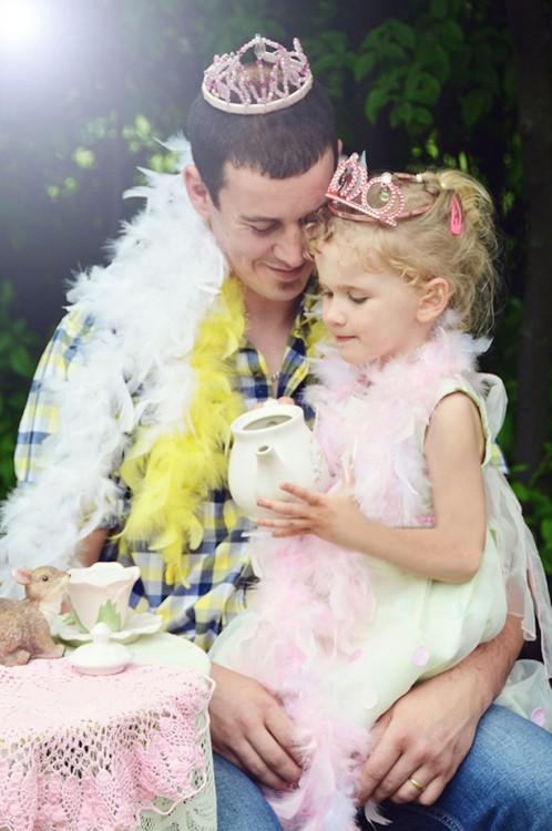 hombre en un jardín cargando a su hija con coronas en su cabeza