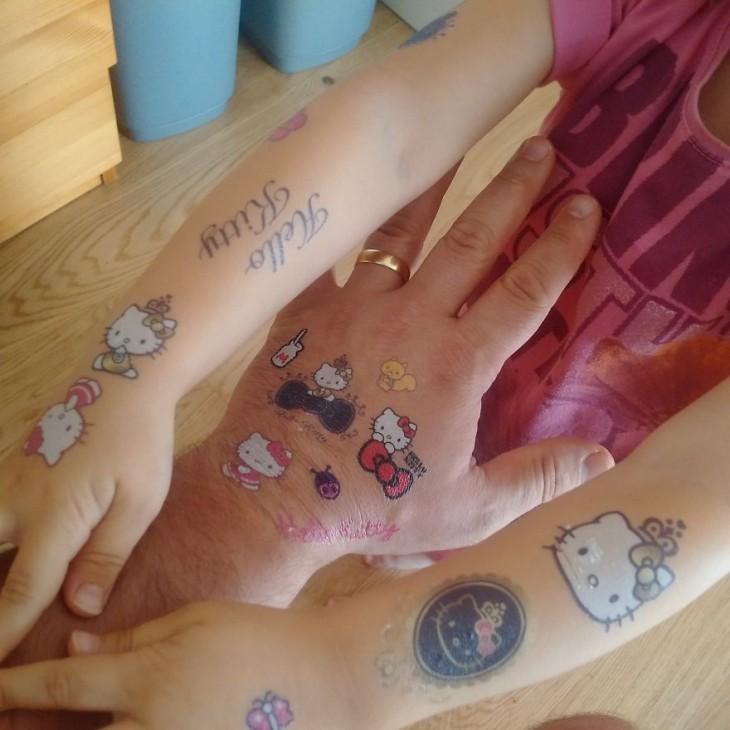 mano de un hombre con tatuajes de hello kitty en medio de los brazos de su hija