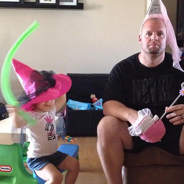 hombre sentado a lado de su hija con una varita mágica y un gorro