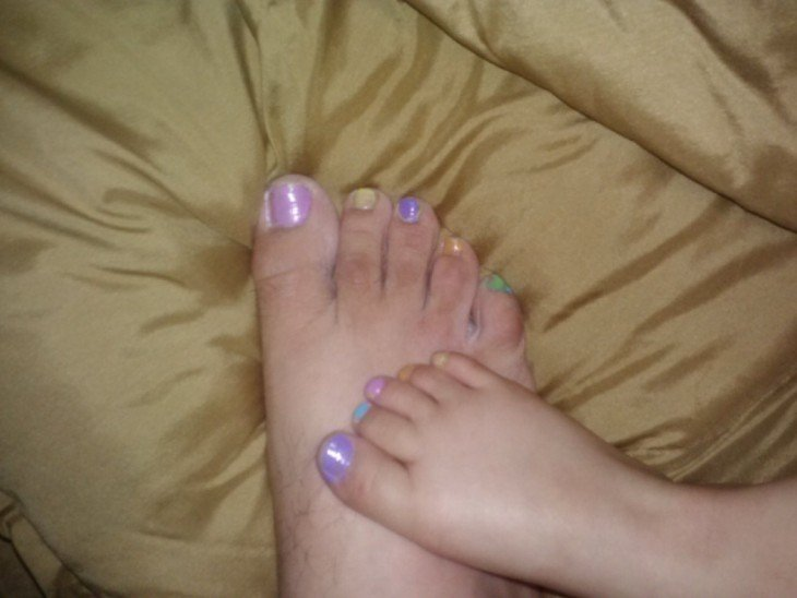 pie de un hombre con las uñas pintadas del mismo color que las del pie de su hija