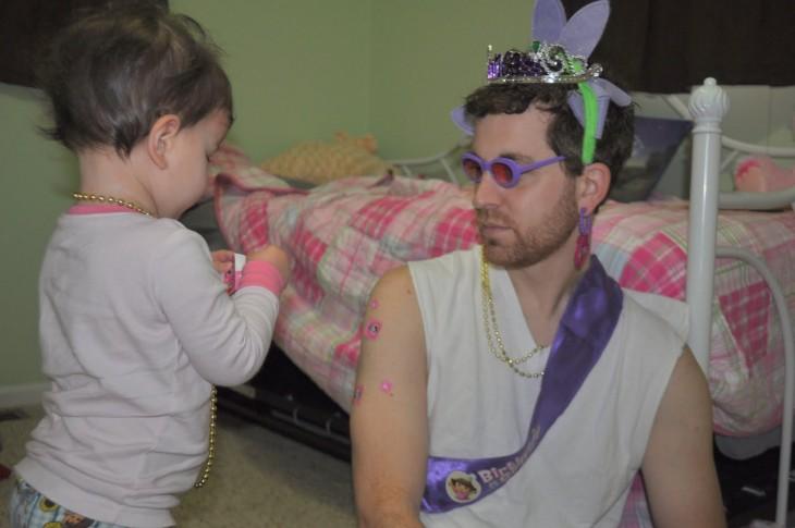 Bebé adornando a su papá con coronas y collares