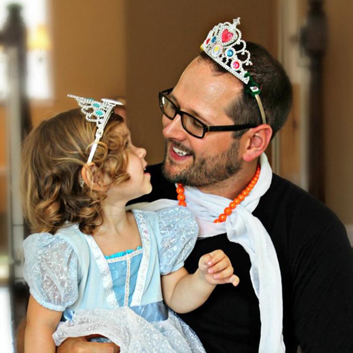 hombre con una corona en su cabeza cargando a su hija vestida de princesa
