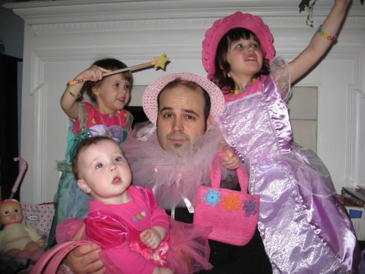 hombre rodeado de sus hijas con un sombrero de color rosa