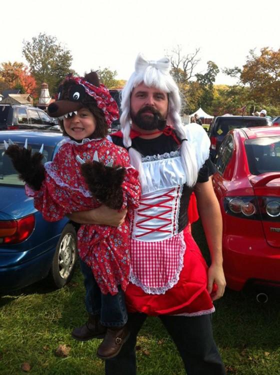 Hombre vestido de Caperucita Roja cargando a una niña vestida de hombre lobo