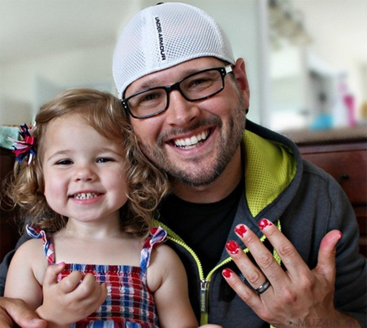 Hombre junto a su niña mostrando sus uñas pintadas en color rojo