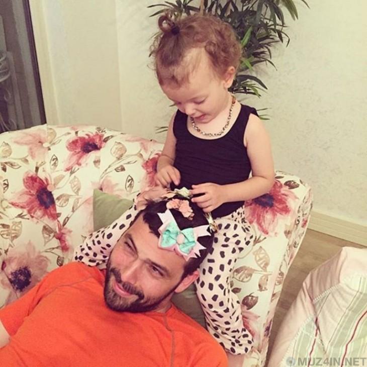niña sentada sobre la cabeza de su papá poniendo broces en su cabello