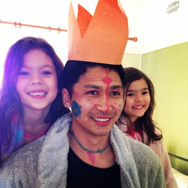 hombre en medio de sus dos hijas pintado de la cara y con una corona de papel en su cabeza