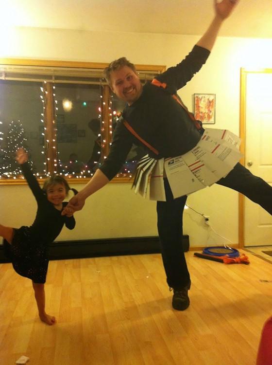Hombre con una falda hecha de papel bailando a lado de su hija
