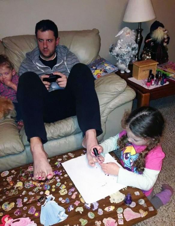 hombre sentado en un sillón jugando videojuegos mientras su hija le pinta las uñas