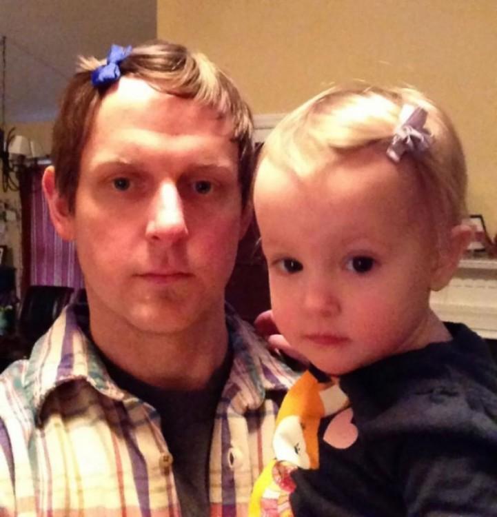Padre cargando a su pequeña hija en donde lucen el mismo peinado